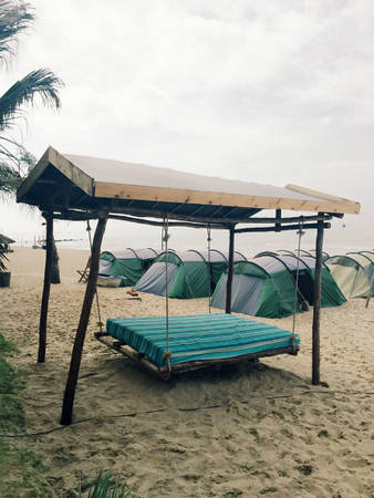 Chiếc giường nệm đong đưa trên bãi cát.