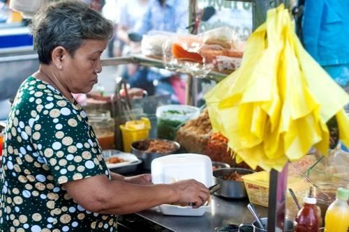 Cạnh đó là một bác bán hàng lớn tuổi đang làm món bánh tráng trộn cho nhóm khách du lịch nước ngoài. Bánh tráng trộn là món ăn đặc sản Sài Gòn và các tỉnh miền Nam mà bạn không nên bỏ qua.