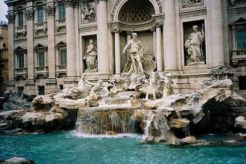 """Đài phun nước Trevi Đài phun nước Trevi là một trong những địa điểm đẹp nhất của thành Rome. Ngọn nước lấp lánh chảy ra từ cổng dẫn nước lâu đời nhất ở Rome thường được gọi là """"Acqua Virgine"""" (ngọn nước thiêng). Nổi bật ở giữa hồ là bức tượng uy nghi của Neptune, vị thần biển cả, đang đứng hiên ngang trên cỗ xe được thắng cương bởi những chú ngựa biển oai dũng. Đừng quên ném một đồng xu trước khi rời khỏi vì theo truyền thuyết nếu để lại một đồng xu ở đài phun nước này, bạn sẽ có cơ hội trở lại thành Rome."""