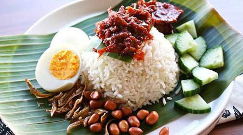 Nasi Lemak (cơm dừa truyền thống) Món cơm dừa là đồ ăn truyền thống của Malaysia, gồm có cơm trắng nấu nước cốt dừa phục vụ trên lá chuối (hoặc bát đĩa có hình lá chuối) cùng cá cơm chiên, lạc rang, dưa chuột và trứng luộc thái lát. Ngoài ra có thể ăn cùng mực, thịt gà, sò, thịt bò rendang và rau muối.