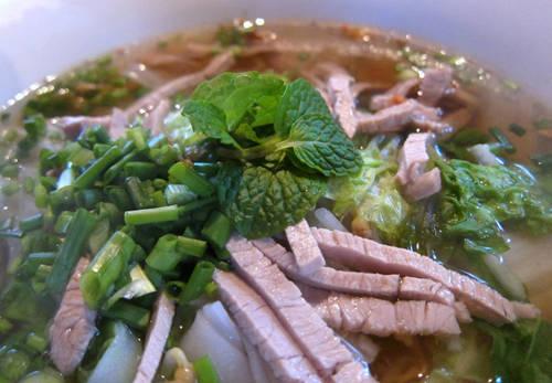 Mì Lào Một bát mì đơn giản với nước dùng, mì, các loại rau như húng quế, giá đỗ, bạc hà và ớt.