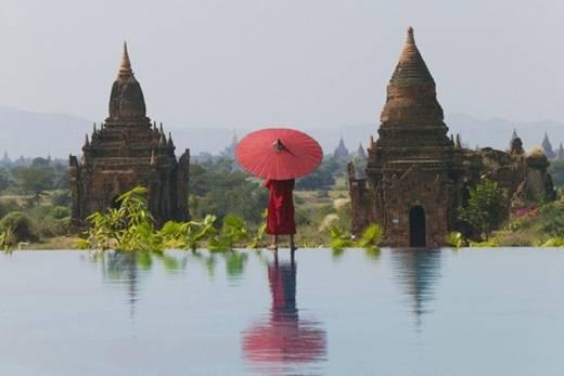 Nhà sư với chiếc ô đỏ tần ngần trước bốn bề thiên nhiên rộng lớn. (Nguồn: Internet)