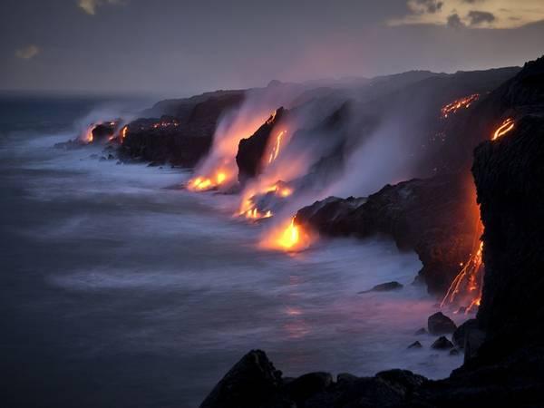 Công viên quốc gia núi lửa Hawai, Mỹ: Tới đây, du khách sẽ được chiêm ngưỡng cảnh tượng nham thạch đỏ rực chảy vào Thái Bình Dương. Ngoài ra, bạn sẽ còn được khám phá những bờ biển, rừng mưa và hệ động thực vật hoang dã của công viên này. Ảnh: National Geographic.