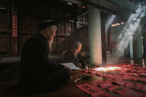 Hai cụ ông trong trang phục truyền thống ở Long Sơn (Bà Rịa - Vũng Tàu) viết câu đối để chuẩn bị đón năm mới. Ảnh: JetHuynh/Picfair.