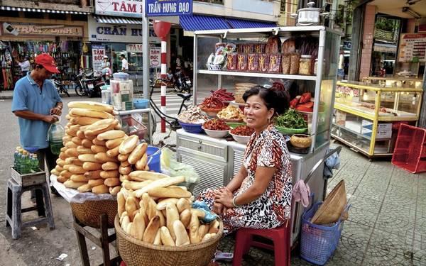 Thưởng thức ẩm thực đường phố Việt Nam: Từ những người bán rong gánh hàng trên vai, tới xe đẩy, quầy ăn ở chợ hay trên vỉa hè, ẩm thực đường phố Việt Nam sẽ đem lại cho du khách những trải nghiệm khó quên. Ảnh: Roughguides.