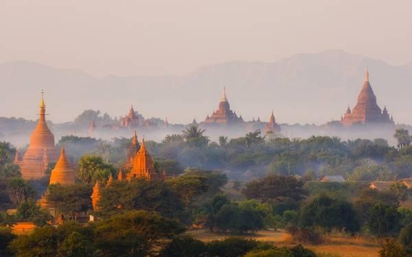 Ngắm bình minh ở Bagan, Myanmar: Cố đô Bagan của Myanmar nổi tiếng với vẻ đẹp thần tiên, với hàng nghìn đền chùa, bảo tháp rải rác khắp vùng, nhô lên giữa cây cối xanh tươi. Khi ánh bình minh lộng lẫy chiếu xuống Bagan, những khinh khí cầu đủ màu sắc lửng lơ trên làn sương mỏng. Du khách sẽ thấy choáng ngợp trước vẻ đẹp tưởng chừng như không có thật của vùng đất này. Ảnh: Roughguides.
