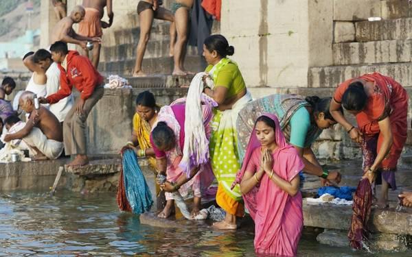 Đi thuyền dọc sông Hằng, Ấn Độ: Từ trên thuyền, bạn sẽ được chiêm ngưỡng những bậc thang đá được điêu khắc cầu kỳ dọc bờ. Các tín đồ và người dân đổ về đây để thực hiện nghi lễ chào đón bình minh hay tắm giặt. Ảnh: Roughguides.