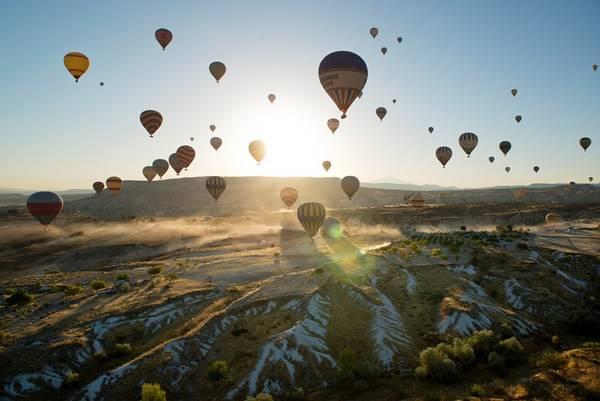 """Chiêm ngưỡng khung cảnh siêu thực ở Cappadocia, Thổ Nhĩ Kỳ: Vùng đất xinh đẹp này có các tháp đá kỳ lạ được ví như """"ống khói tiên"""". Khi những tia sáng đầu tiên chiếu xuống, khung cảnh như trên mặt trăng dần lộ ra trên nền trời rực rỡ. Đừng bỏ lỡ cơ hội chiêm ngưỡng Cappadocia từ khinh khí cầu. Ảnh: Roughguides."""