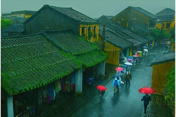 """Năm 2014, trong một lần ngắm mưa ở phố cổ Hội An (tỉnh Quảng Nam), Nguyễn Hữu Khiêm đã ghi lại khoảnh khắc này. Tác giả đặt tên cho bức ảnh là """"Trong mưa""""."""