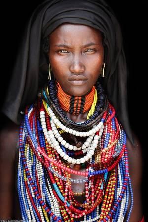 Phụ nữ của tộc Arbore che đầu bằng khăn vải đen, đeo những chiếc vòng cổ và hoa tai có màu sắc rực rỡ.