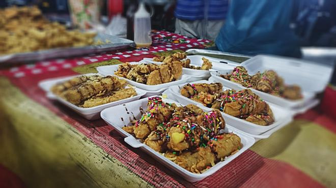 Chuối chiên phủ cốm là biến tấu lạ cho món quà vặt quen thuộc ở Bazar. Chuối dùng để chiên có độ săn, sần sật như chuối sáp. Món ăn này không có độ giòn như chuối chiên Việt Nam. Giá một phần là 2 RM (11.000 đồng). Món ăn vặt ngon, rẻ ở chợ đêm Langkawi