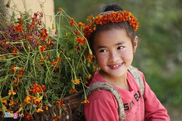 Bé Lý Thị Khiêu (9 tuổi) ở xã Sủng Là đeo gùi hoa chụp ảnh cùng du khách. Sau mỗi tấm hình, bé sẽ được các cô, chú, anh, chị cho tiền.