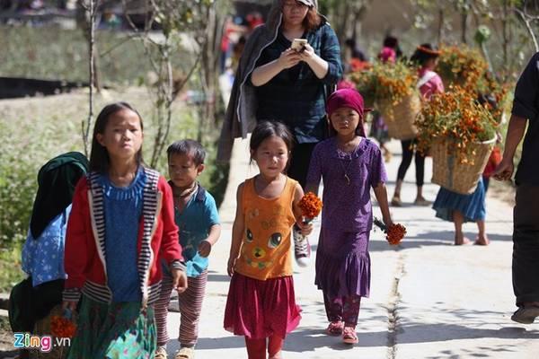 Những em nhỏ người dân tộc được huy động đi bán hoa phục vụ khách chụp ảnh.