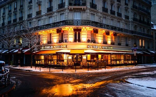 Quán cà phê mở cửa vào sáng sớm, với ánh đèn vàng ấm áp.