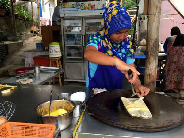 Một phụ nữ đạo Hồi làm món bánh Pancake chuối - Ảnh: Thủy OCG