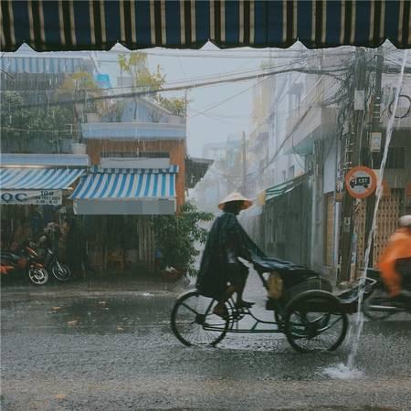 Sài Gòn mưa, những người lao động bé nhỏ vẫn xé màn mưa mà đi. (Ảnh: Âu Dương Thành)