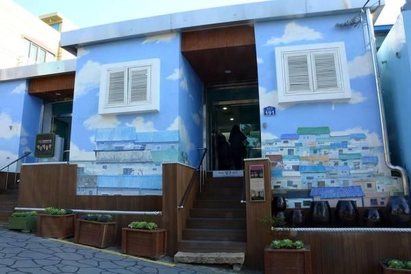 Bước đến đầu làng, bạn sẽ ấn tượng ngay với ngôi nhà màu xanh sơn vẽ các công trình đặc trưng ở Gamcheon. Đây cũng là nơi du khách bắt đầu hành trình khám phá làng văn hóa theo tấm bản đồ Gamcheon lấy tại quầy thông tin.