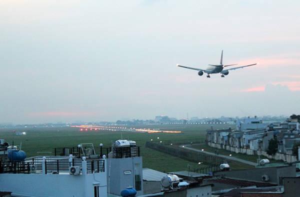 Hoàng hôn sân bay Tân Sơn Nhất, rực ánh đèn pha từ đường băng. Ảnh: Zen Nguyễn