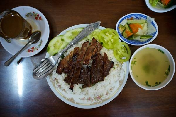 Bai sach chrouk (Cơm thịt heo): Đây là món ăn rất đơn giản nhưng ngon tuyệt, phổ biến khắp xứ chùa tháp. Thịt lợn thái mỏng, nướng từ từ trên than đá để giữ được vị ngọt tự nhiên. Đôi khi thịt lợn có thể được ướp nước cốt dừa và tỏi. Thịt được bày trên cơm tấm, với dưa góp và gừng. Bạn sẽ có thêm một bát nước dùng gà để ăn cùng. Ảnh: Nyampenh.