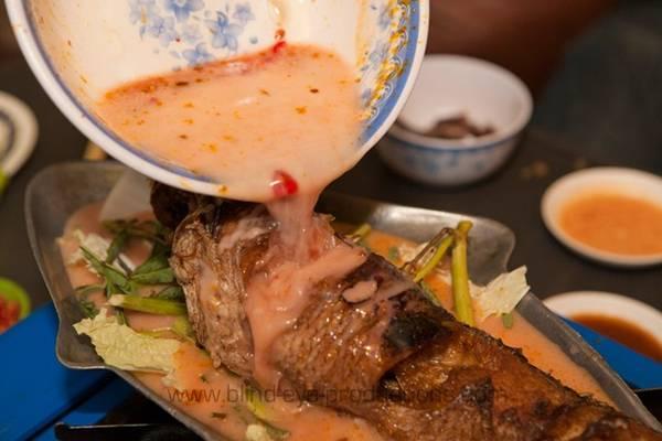 Cá om: Cá được rán nguyên con, sau đó cho lên nồi lẩu cùng cà ri cốt dừa cay ngọt, thêm các loại rau như bắp cải, ăn kèm mì gạo. Ảnh: Blind-eye-productions.