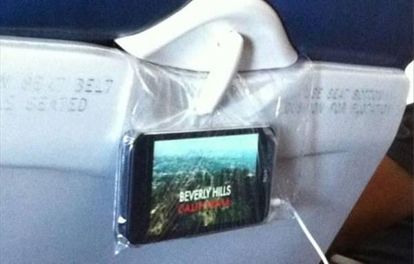 Dùng túi nilon để treo điện thoại: Cho điện thoại vào túi, kẹp miệng túi vào chiếc bàn gấp phía trước, thế là bạn đã có chiếc TV mini.