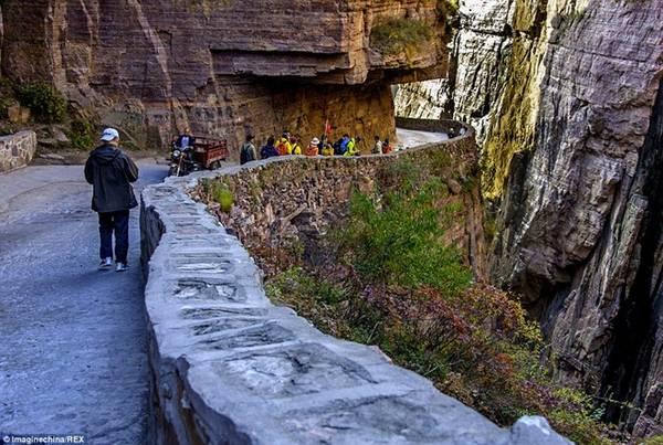 Đường hầm gập ghềnh, dốc và hẹp này rất trơn lúc trời mưa. Do đó, du khách cần cực kỳ thận trọng khi tới đây vào lúc thời tiết không thuận lợi. Cơ hội sống sót không cao nếu ngã khỏi vách đá. Ảnh: Imaginechina/REX.
