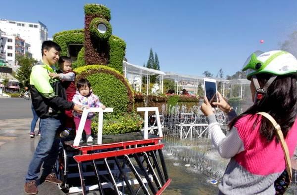 Một gia đình thích thú chụp hình bên đoàn tàu kết bằng hoa ở đài phun nước trước chợ đêm Đà Lạt sáng 28-12- Ảnh: C.THÀNH