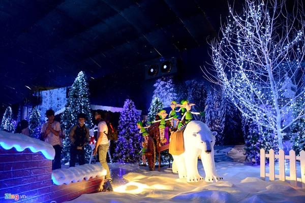 Gấu Bắc cực kéo xe trên nền tuyết phủ, xung quanh có nhiều cây thông.