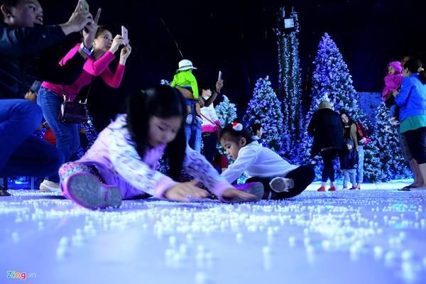 Người lớn chụp ảnh, trẻ em chơi những hạt tuyết bằng xốp trên sàn.