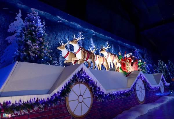 Mô hình đàn tuần lộc kéo xe chở ông già Noel băng qua mái nhà.