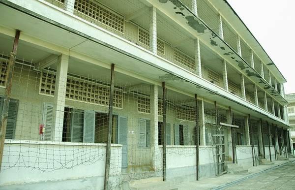Dãy lớp học tại Tuol Sleng được bao bọc bởi hàng rào dây thép gai.