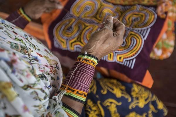 Một người phụ nữ Kuna Yala đang may một chiếc Mola có họa tiết phức tạp. Ảnh: Nori Jemil