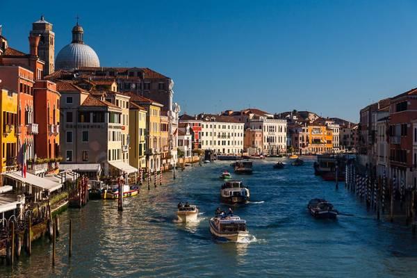 Những tòa nhà rực rỡ sắc màu bên dòng kênh phẳng lặng, nhộn nhịp tàu qua lại.