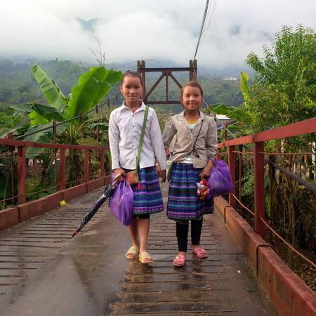 Hai em bé dân tộc đi dạo trên cầu ở Tả Van vào sáng sớm. Ảnh: Tùng Neo.