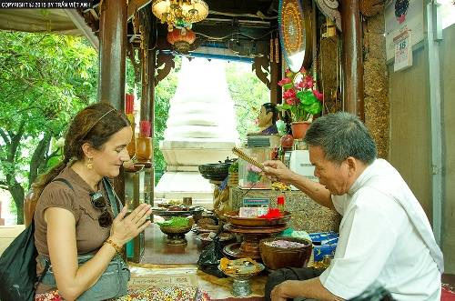 Một du khách Pháp đang được thầy cúng làm phép ở Wat Phnom. Ảnh: Trần Việt Anh