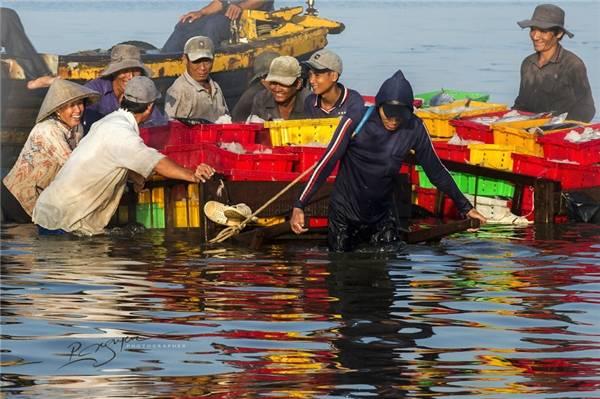 Lao động vất vả là thế nhưng nụ cười hồn hậu vẫn nở trên môi những người dân làm việc tại cảng cá. (Ảnh: Nguyễn Vũ Phước)
