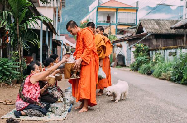 Nhà sư đi khuất thực trên đường phố Vang Vieng. Ảnh: Ahmad Syukaery