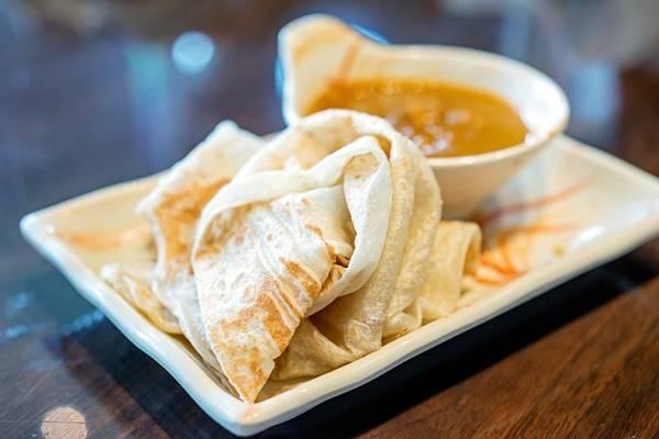 <strong>Roti canai:</strong> Đây là món ăn sáng điển hình của Malaysia, có nguồn gốc từ Ấn Độ. Tuy nhiên, bạn có thể thưởng thức vào bất cứ thời điểm nào trong ngày. Bột mì, trứng và ghee (bơ đun chảy và bỏ bớt nước) được trộn đều, tán mỏng trên chảo nướng và sau đó gập lại. Món này rất ngon khi ăn nóng, với ruột mềm và vỏ giòn. Roti canai thường được dùng kèm cà ri. Ảnh: Michael Shum/Flickr.