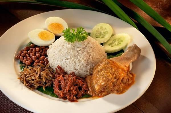 Nasi lemak: Đây được coi là món ăn biểu trưng của Malaysia với nguyên liệu phong phú và cách trình bày đẹp mắt. Cơm nấu cốt dừa được cho lên lá chuối xanh, rưới sốt sambal cay, cá trống khô, lạc rang, dưa chuột, trứng (luộc hoặc ốp la), đôi thi có thêm thịt gà hoặc hải sản. Ảnh: Touristic360.