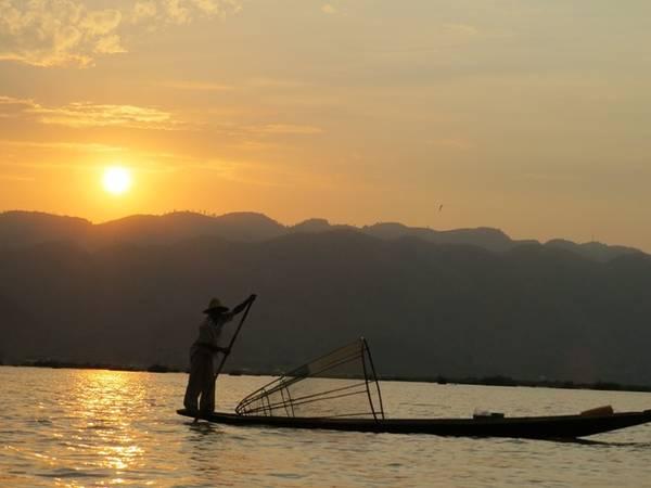 Ngư dân chèo thuyền bằng một chân trên hồ.