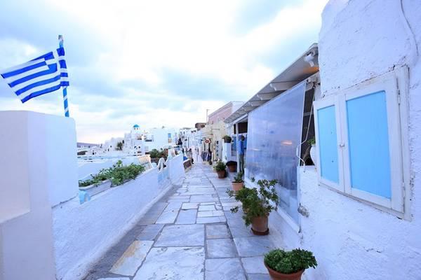Oia là điểm đến cuối cùng trong ngày của chúng tôi. Nơi đây được mệnh danh là địa điểm ngắm hoàng hôn đẹp nhất thế giới. Từ 16h, chúng tôi đã có mặt tại làng, loanh quanh trên những bậc đá uyển chuyển, điệu đà dưới tán hoa giấy, bên những ngôi nhà tường trắng mái và cổng xanh nổi tiếng.