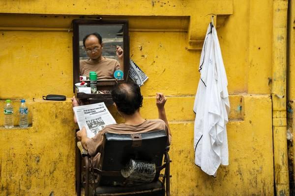 Một mảng màu bình dị trong cuộc sống thường nhật ở thủ đô Hà Nội: người thợ cắt tóc chăm chú đọc báo trong lúc chờ khách hàng.