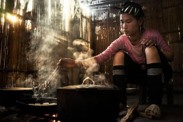 Một thiếu nữ dân tộc ở Sapa nấu cơm trong ánh nắng chiếu qua vách. König cho biết những món ăn ở đây rất ngon.