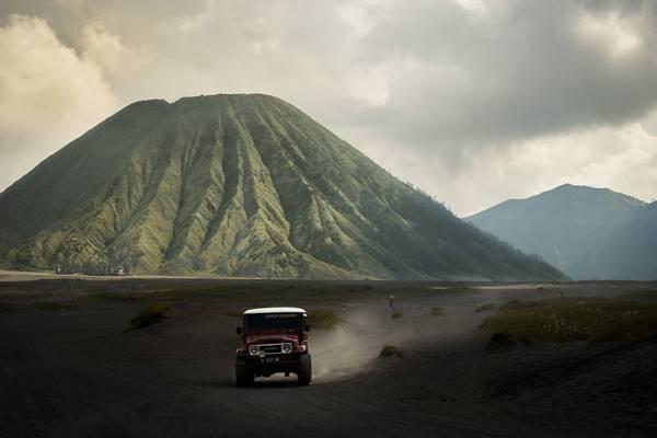 Chiếc ôtô chở khách đi trên nền tro bụi núi lửa, với phông nền là ngọn núi Bromo hùng vĩ có thể khiến bất cứ ai có tinh thần phiêu lưu muốn xách balô lên và đi.
