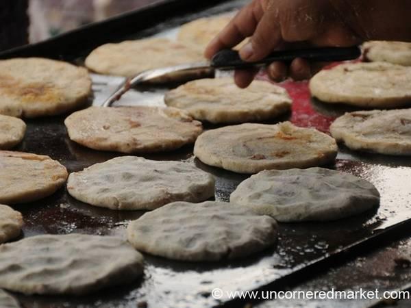 El Salvador: Pupusa gồm lớp vỏ bánh từ ngô, với nhân đậu đỏ, phô mai và chicharron (thịt ba chỉ rán), thêm dưa góp và ớt lên trên. Món này vừa rẻ, vừa no bụng và dễ tìm. Ảnh: Uncornered Market.