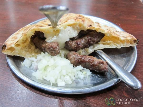 Bosnia và Herzegovina: Đi dọc đường phố Sarajevo, bạn sẽ không thể nào không ngửi thấy mùi ćevapi, món thịt nướng nổi tiếng của người Bosnia. Ćevapi thường gồm 5-10 viên thịt băm nướng được kẹp trong bánh mì tròn hoặc bánh mì dẹt. Bạn có thể cho thêm hành hoặc kem ofkajmak. Ăn xong một suất ćevapi, bạn sẽ thấy no cả ngày. Ảnh: Uncornered Market.