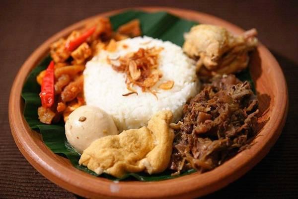 Gudeg: Gudeg là đặc sản của thành phố Yogyakarta. Mít được hầm hàng tiếng liền cùng nước dừa, đường cọ cho tới khi mềm. Món ăn ngọt ngào này được thêm một số gia vị, trong đó có lá tếch để tạo màu nâu hấp dẫn. Gudeg được ăn cùng cơm, trứng luộc, gà và da bò chiên giòn. Ảnh: Wonderfuljogja.