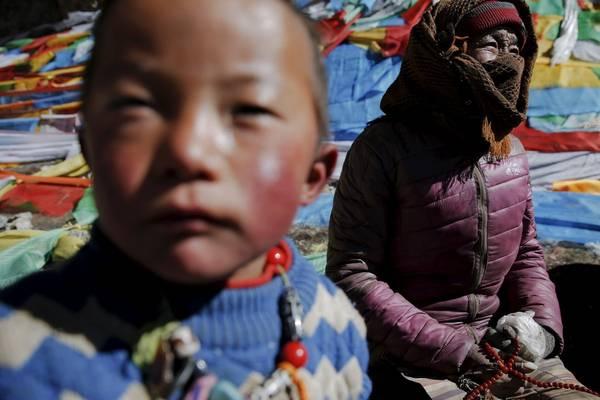 Bà mẹ và cậu con trai đang cầu nguyện gần hồ Namtso. Ảnh: Damir Sagolj / Reuters