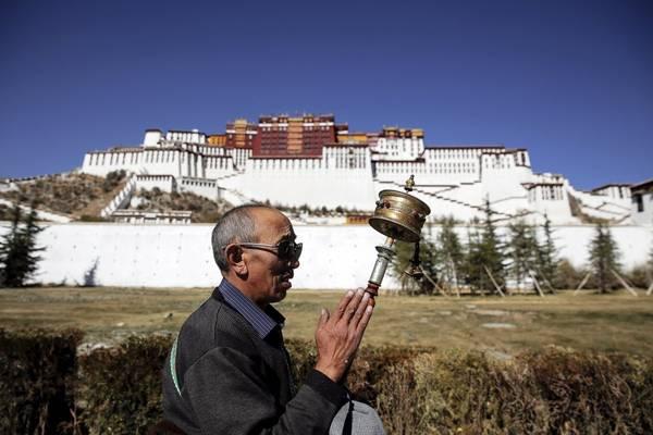 Một người đàn ông đang cầu nguyện trước Cung điện Potala. Cung điện này đã hơn 1.300 năm tuổi và từng là chốn tu hành của các vị Đạt Lai Lạt Ma tới đời thứ 14, tượng trưng cho Phật giáo Tây Tạng và đóng vai trò gìn giữ, truyền bá văn hóa truyền thống của Tây Tạng. Ảnh: Damir Sagolj / Reuters