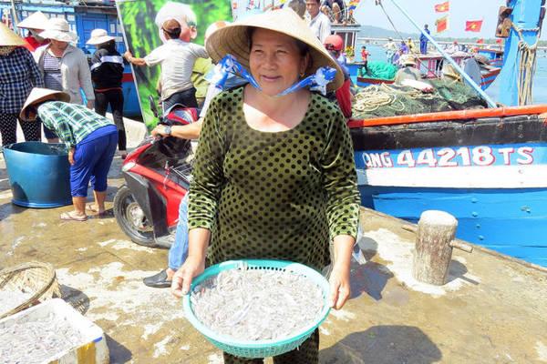 Một tiểu thương hớn hở vừa thu mua được rổ cá cơm mồm tươi rói - Ảnh: Minh Kỳ